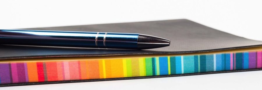 Pen resting on a notebook with multicoloured pages
