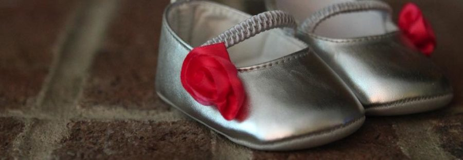 A pair of silver and red baby shoes