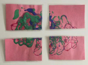 Puzzle painting: green, blue and pink swirls on pink paper