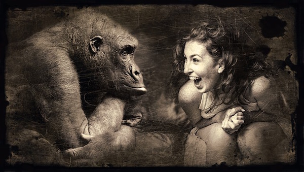 Woman sitting next to an ape and laughing