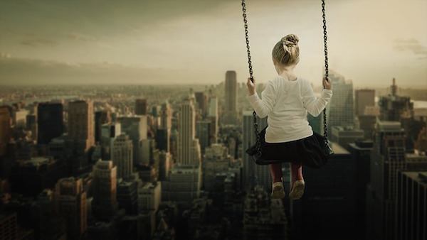 Girl on swing over city