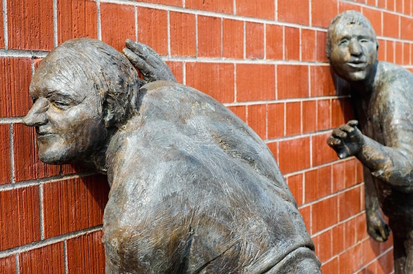 Sculptures listening at brick wall